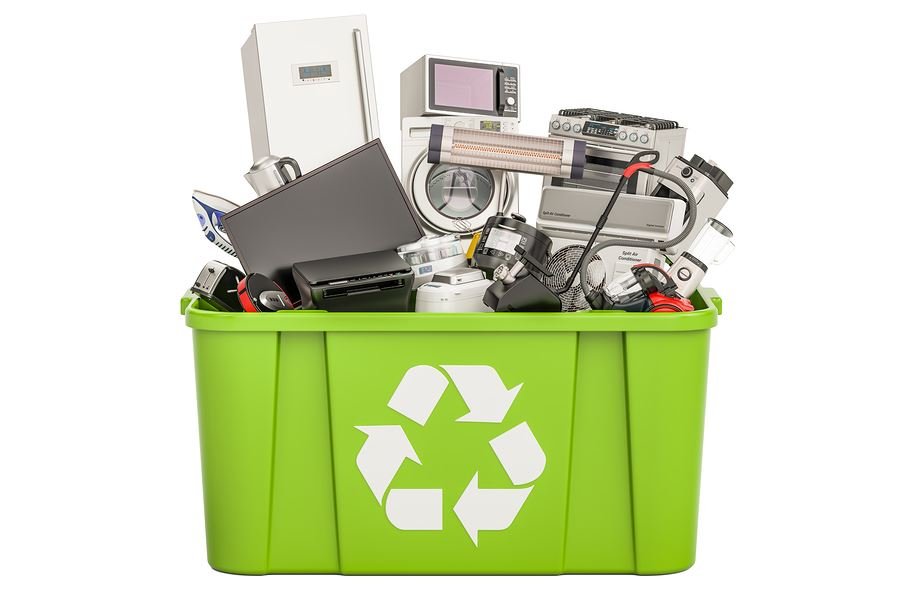 Image of electronics in a green recycling bin.